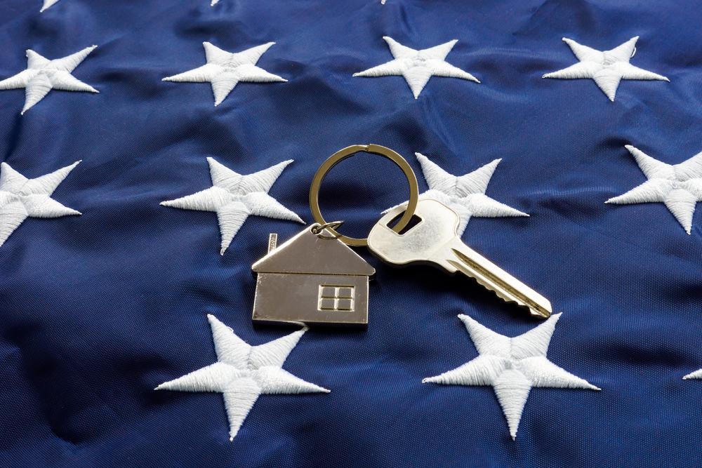 va loan | key with house keychain laid on United States Flag